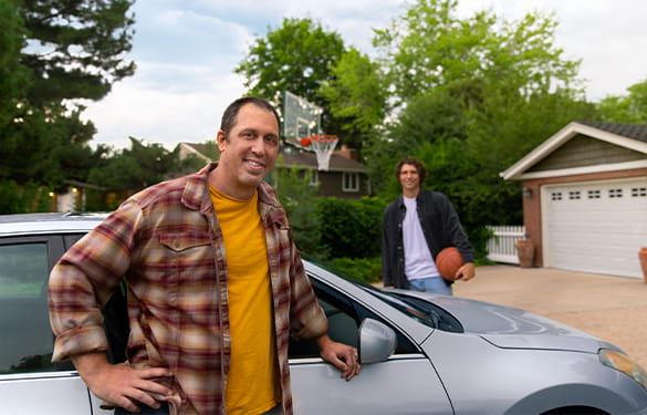 Father and a basketball-holding son standing by car in driveway