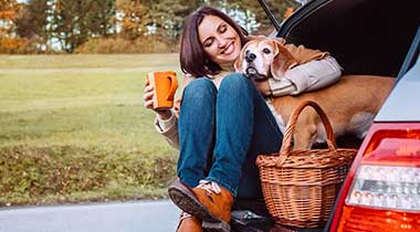 woman and dog having a coffee in a car