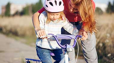 mom teaching daughter to ride bike