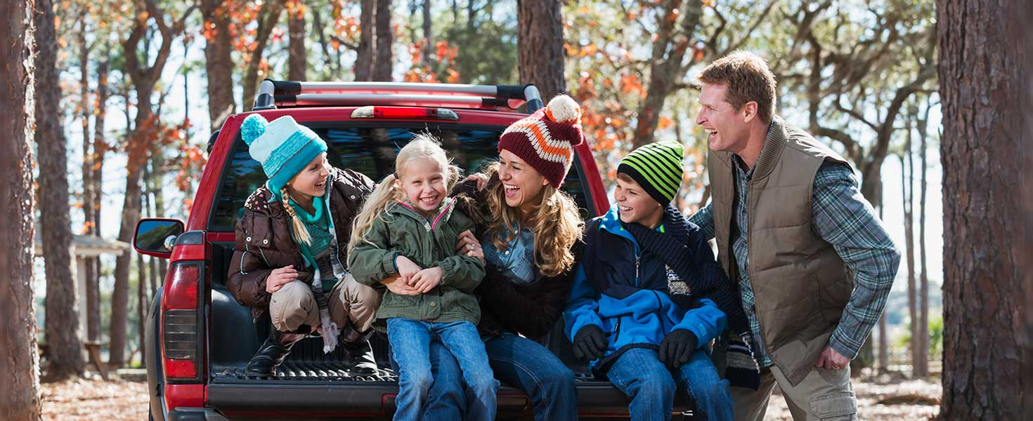 parents and kids having fun in the woods at the tailgate of their car