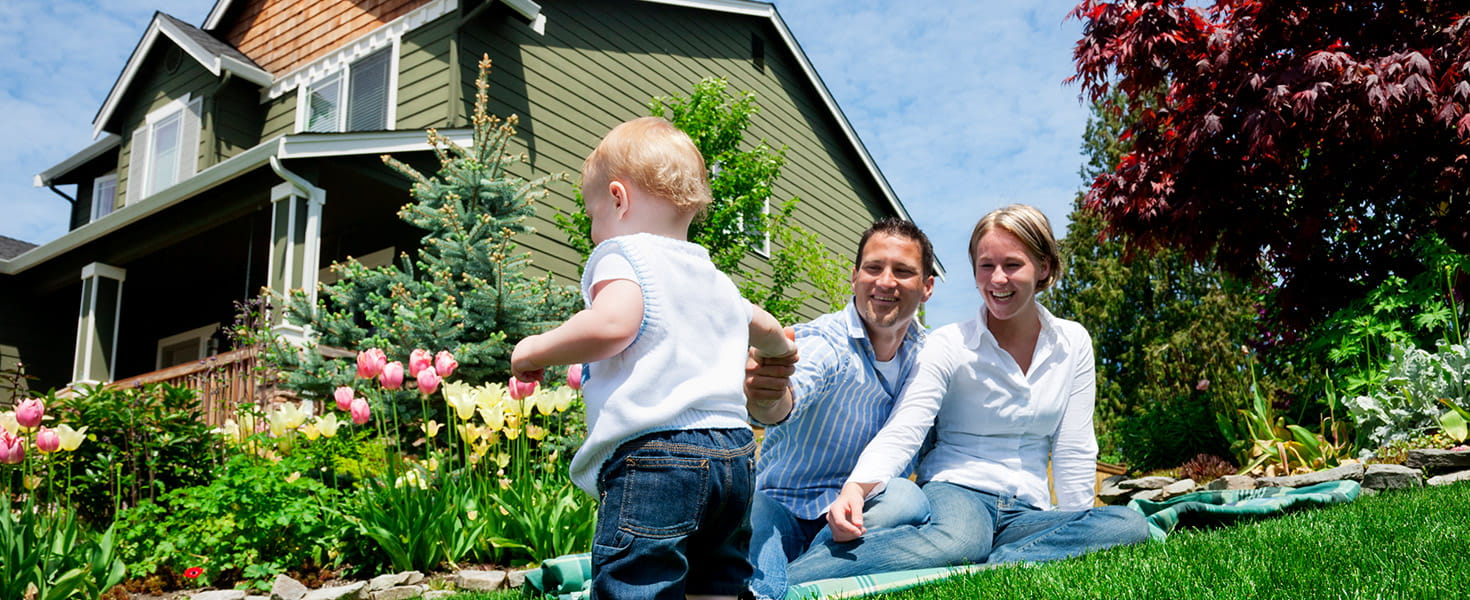 family with baby in front yard of home