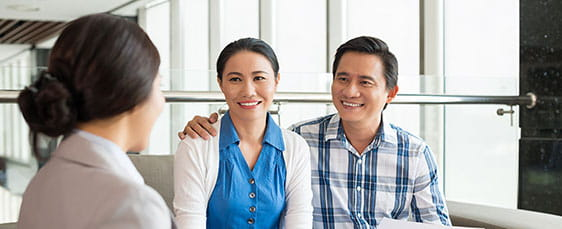 smiling couple talking with agent