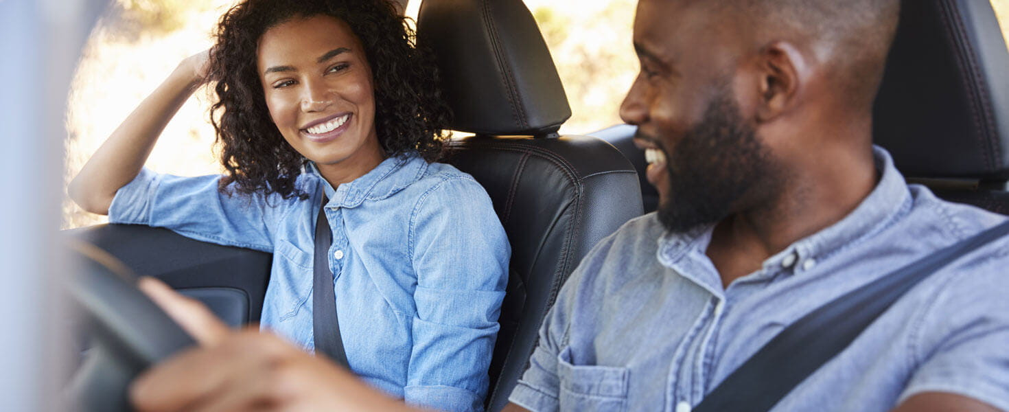 A happy couple drive down the road with confidence knowing if they need roadside assistance AAA will be there.
