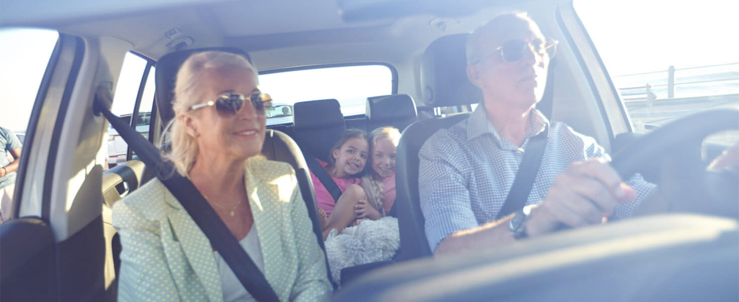 Grandparent driving with their grandchildren