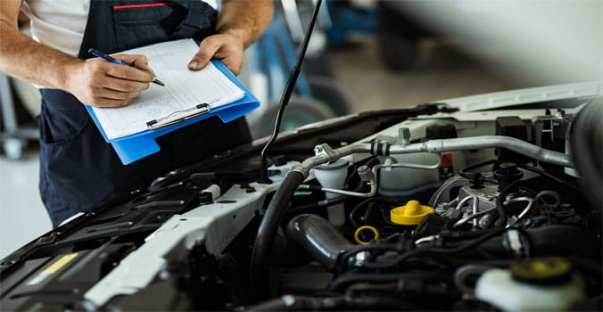 Mechanic Looking Under Hood of Car