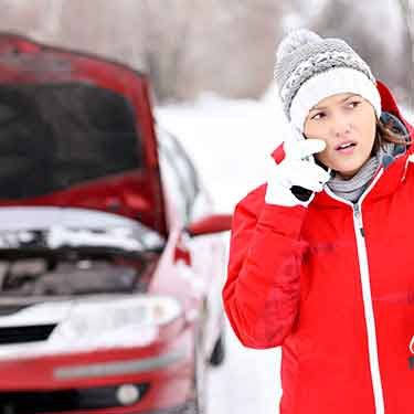 woman on phone in coat hat and mittens in front of car with open hood