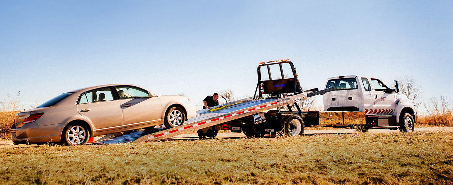 aaa-tow-truck-driver-loading-car-on-to-flat-bed-tow-truck