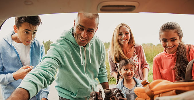 family-looking-in-back-of-trunk-of-car
