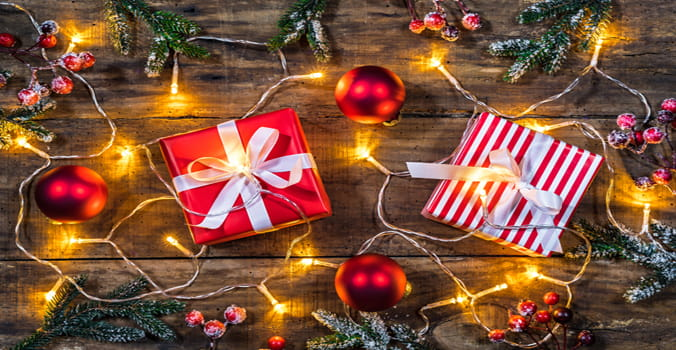 gifts on wooden table surrounded by holiday lighting and holly