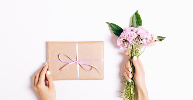 hand_holding_gift_box_and_hand_holding_flower_ bouquet