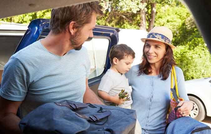 woman in hat holding boy smiling at man loading car