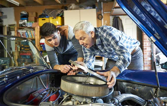 father and son working together on a classic car in a garage with air filter cover open looking in
