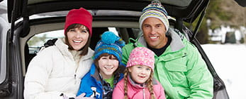 winter family sitting in back of car