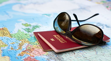A pair of sunglasses sitting on passports and a map
