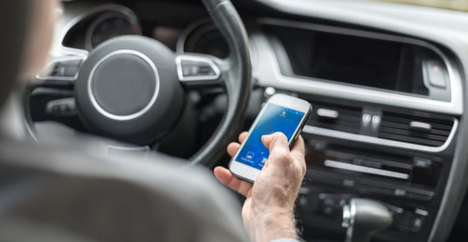 person looking at phone while driving