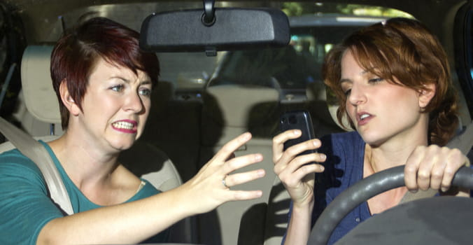 mom trying to take phone away from distracted driving daughter
