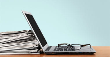 Paper Articles next to a Laptop