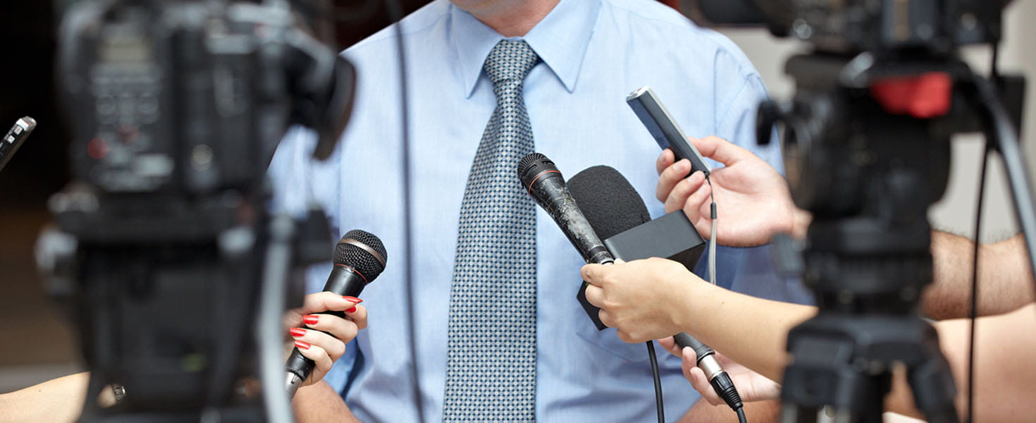 Man being interviewed by multiple news reporters