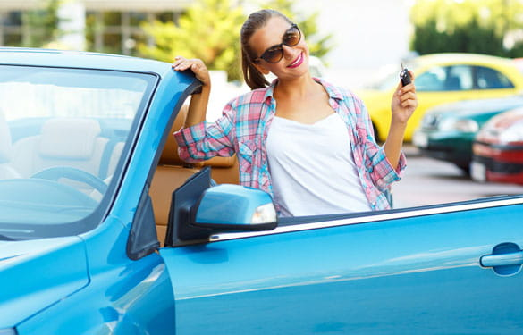 Young lady standing outside of car holding keys on sunny day