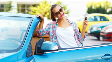 Young pretty woman in sunglasses standing near convertible with keys in hand.
