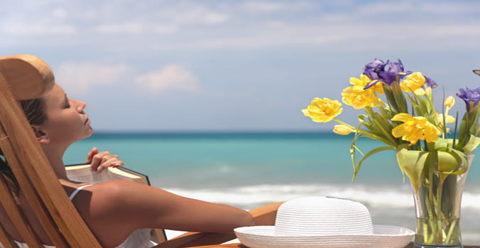 Woman relaxing with book on her chest on the beach