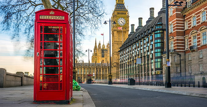 The iconic british old red telephone box with the Big Ben at background in the center of London