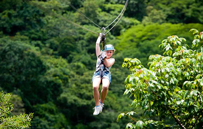 Girl zip lining through rain forest in Costa Rica