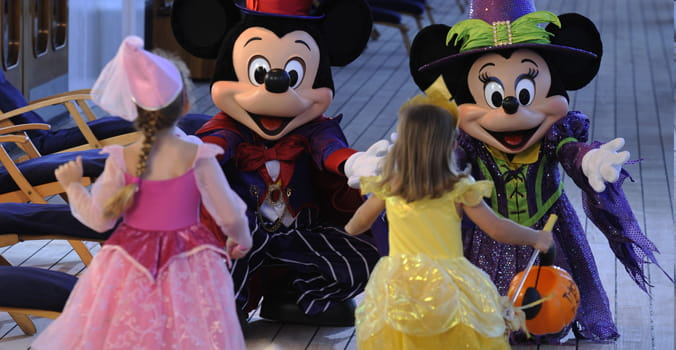Children running to give Mickey and Minney a hug while trick-or-treating