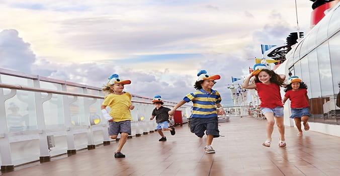 Little kids running along the deck of a Disney Cruise ship