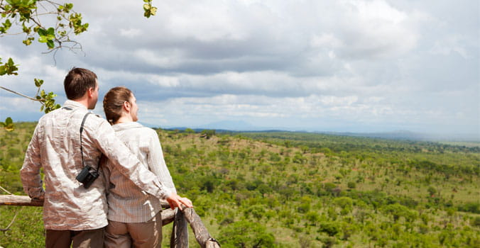 Couple on safari vacation looking to savanna from balcony