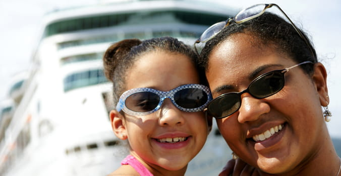 Mom and daughter standing on the deck of a cruise ship in sunglasses