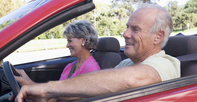 Retired couple driving in a convertible