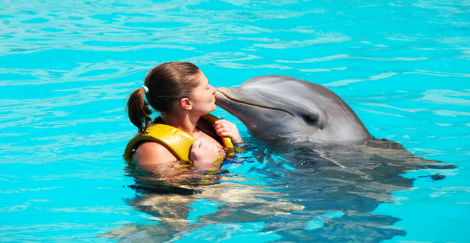 Woman kissing dolphin in a pool
