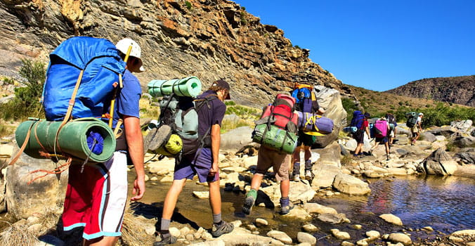 Hikers cross small river in the mountains of Western Cape, South Africa