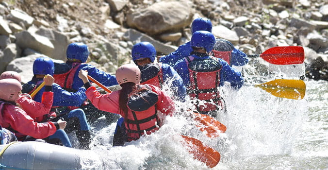 Group of men and woman white water rafting