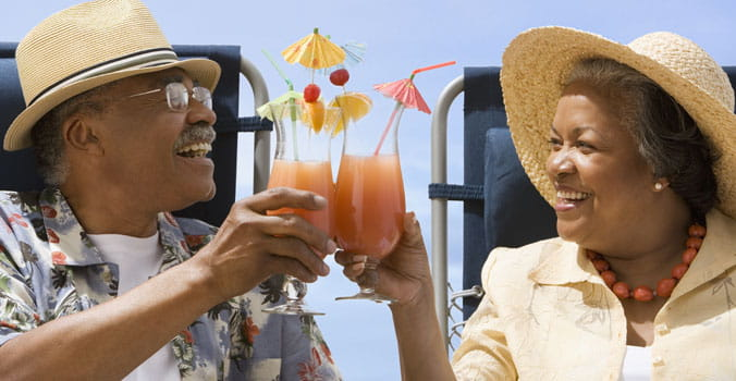 Retired couple saying cheers with their cocktails while on vacation