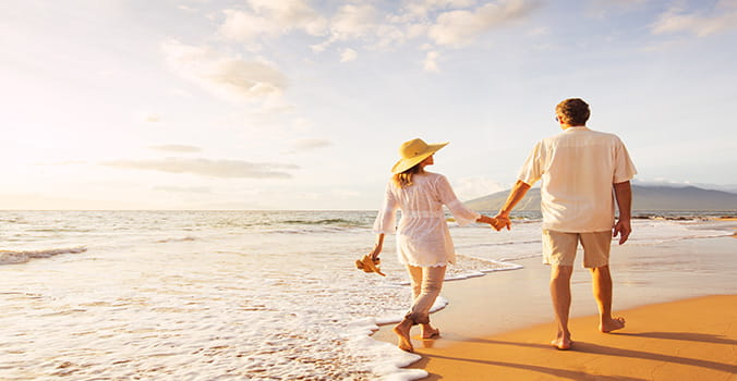 Man and Woman walking along beach in Hawaii holding hands