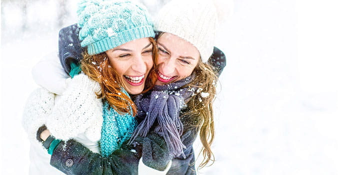 Mother and daughter laughing in the snow.