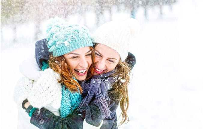 Mother and daughter outside in the snow laughing.