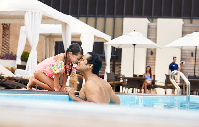Father and daughter playing poolside at Hyatt hotel.