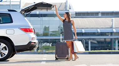 Woman getting luggage out of her trunk in a parking lot