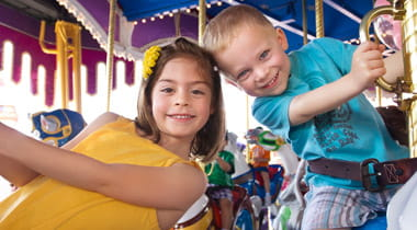 Kids on a Carousel in Amusement Park