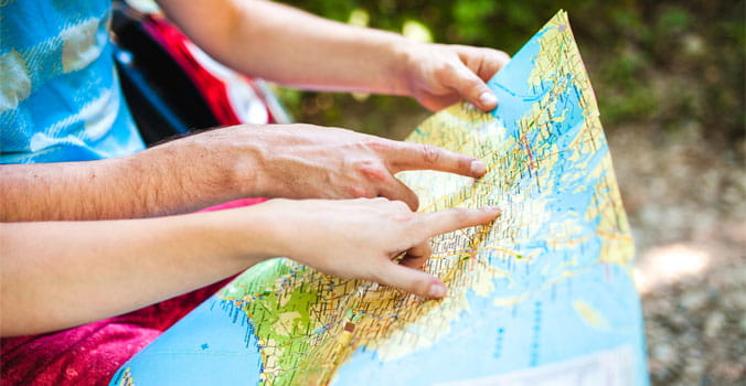 Closeup of hands of travelers looking at a map