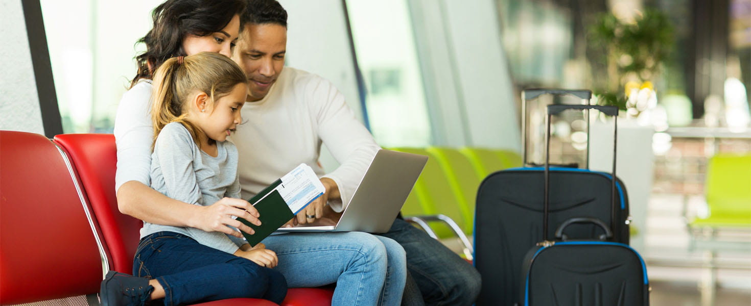 Parents and little daughter using laptop at airport