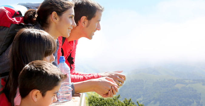 Family backpackers at the mountain looking at the valley view