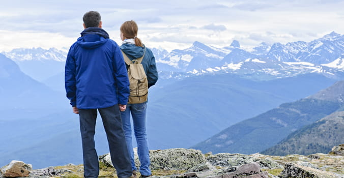 Man and woman standing on top of a moutain looking out
