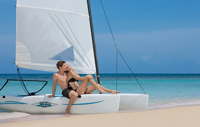 Couple sitting on catamaran in the surf