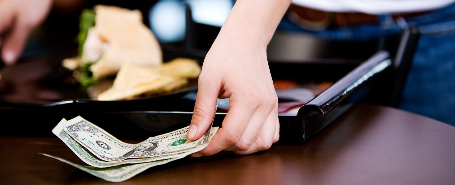 Lady leaving money on table in restaurant