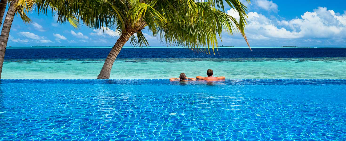 Couple relaxing in infinity pool under palms in front of tropical landscape