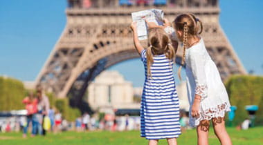 Two girls standing in front of Eiffel Tower.